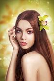 Krása portrét bruneta model s zdravé rovné vlasy s květinou — Stock fotografie