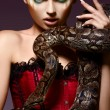 Serpent. Fantasy. Fancy Woman holding Tamed Snake in Hands — Stock Photo