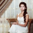 Stock Photo: Femininity. Brown Hair WomBride in Wedding Dress sitting. Classic Romantic Interior