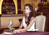 Dating. Dreaming Woman waiting at Decorated Table in Restaurant Interior — Stock Photo