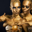 Stock Photo: Masquerade. Enjoyment. Two Glossy Women with Golden Body Art. Glamor