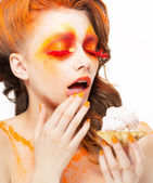 Gilding. Tempting Woman eating a Pie with Cream. Bright Red-Golden Makeup — Stock Photo