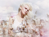 Bloesem. beauty blonde in winderige veld met bloemen. aard. lente — Stockfoto