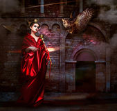 Mysticism. Witchcraft. Sorcerer in Red Mantle with Vulture - Hawk. Ancient Scary Castle — Stock Photo