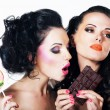 Stock Photo: Relish. Couple of Bright Women with Sweetness - Chocolate and Lollipop