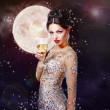 Gorgeous woman with a glass of champagne on the background of a — Stock Photo