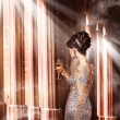 Luxury. Young Woman in Evening Dress with Glass of Champagne Standing at the Window in Sunshine — Foto de Stock