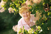 Lively Cheerful Optimistic Senior Woman among Flowers — Stock Photo