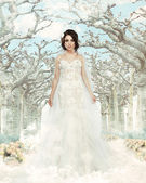 Fantasy. Matrimony. Bride in White Dress over Frozen Winter Trees and Snowflakes — Stock Photo