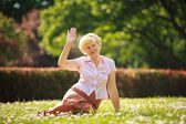 Maturity. European White Hair Woman sitting on Grass and having Fun — Stock Photo