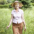 Serenity. Friendly Senior Peasant Woman in Straw in Meadow Smiling — Stock Photo