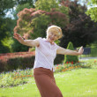Gaiety. Delighted Playful Mature Womwith Outstretched Arms Laughing Outside — Stock Photo #40332297