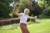 Gaiety. Delighted Playful Mature Woman with Outstretched Arms Laughing Outside — Stock Photo