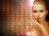 Fantasy. Beautiful Woman over Sparkling Gold Background — Stock Photo