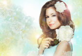 Portrait of Quiet Romantic Woman with Flowers over Colored Bokeh Background — Stock Photo