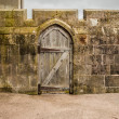 Old wooden door in a stoned wall castle wall — Stock Photo