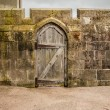 Stock Photo: Old wooden door in stoned wall castle wall