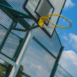 Yellow basket ball hoop at an angle on a summers day — Stock Photo