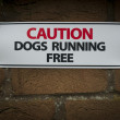 Stock Photo: Warning dogs running free sign on brick wall