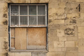 Old wooden sash window half boarded up — Stock Photo