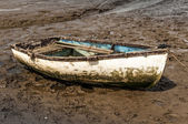 Isolated muddy white rowing boat — Stock Photo