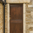 Stock Photo: Brown wooden door set in stone