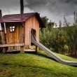 Wooden childrens playhouse with slide — Stock Photo