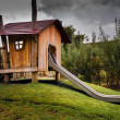 Wooden childrens playhouse with slide — Stock Photo #32149965
