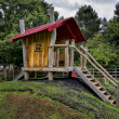 Stock Photo: Childrens wooden playhouse with steps and slide