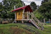 Childrens wooden playhouse with steps and slide — Stock Photo