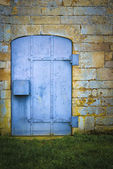 Old blue metal door set in stonework — Stock Photo