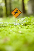 Micro deer caution sign in green forest — Stok fotoğraf