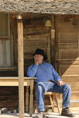 Old cowboy staring into the distance while resting in a chair on his front porch — Stock Photo