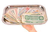 Hand holding tray of world monies, isolated on white — Stock Photo