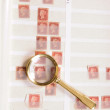 Magnifying glass laying on stamp album — Stock Photo
