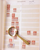 Magnifying glass laying on stamp album — Foto Stock