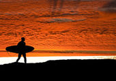 Surfer heading for ocean as the sun sets — Stock Photo