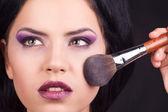Portret pięknej kobiety z makijażu szczotki w pobliżu twarzy — Zdjęcie stockowe