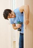 Man repairing the door handle furniture — Stock Photo