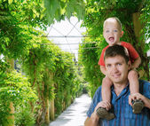 Boy sits on shoulder beside father — Stock Photo