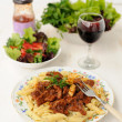 Pasta with meat sause, green salad and wine — Stock Photo #50878825