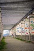 Dirt road with columns painted with graffiti — Stock Photo