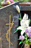 Tombstone with cross and flowers — Stock Photo