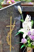 Grafsteen met grensoverschrijdende en bloemen — Stockfoto