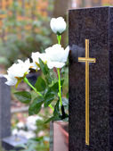 Tombstone with cross and white roses — Stock Photo