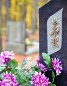 Tombstone with golden rose and purple flowers — Stock Photo