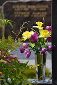 Colorful flowers in a vase on a grave — Stock Photo