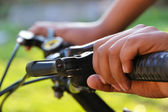 Hands holding the handlebars on the bike — Stock Photo