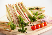 Different sandwiches on wooden desk — Stock Photo