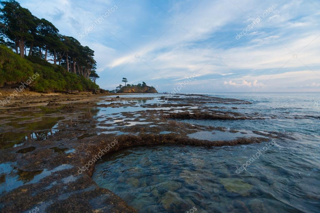 Tide pools collect water on a typically beautiful evening on the rugged coast of Neil Island of the Andaman and Nicobar chain of islands in India — Stock Photo #14897333